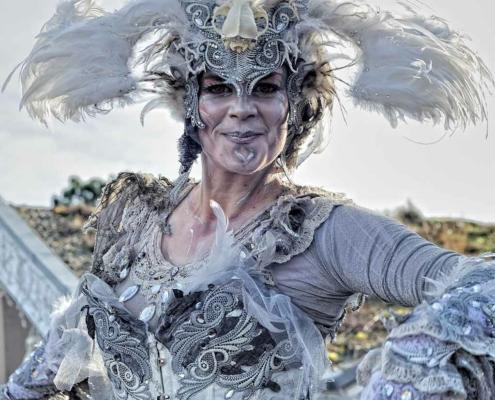 Phantastische Figur mit flügelbesetztem Kopfschmuck und weiß, silbernem Kostüm