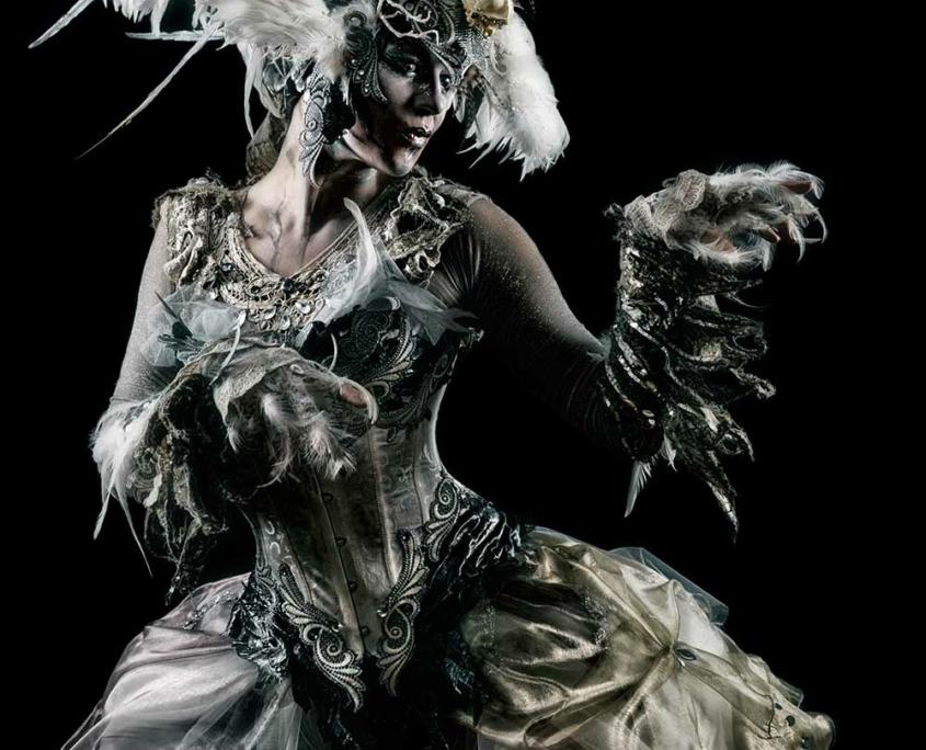 Phantastisches, vogelartiges Kostüm mit Krallen und großem Kopfschmuck in weiß und silber