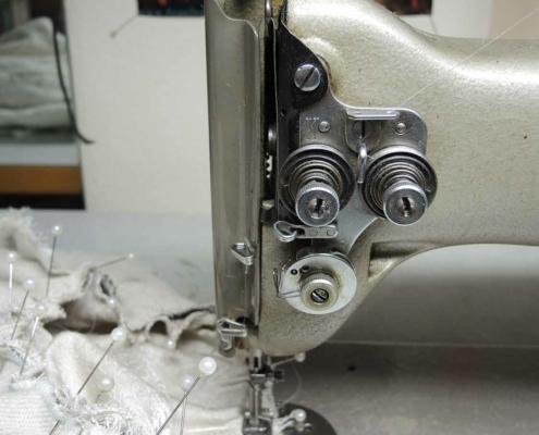 Nähmaschine mit Stoffstück in dem viele weisse Nadeln stecken