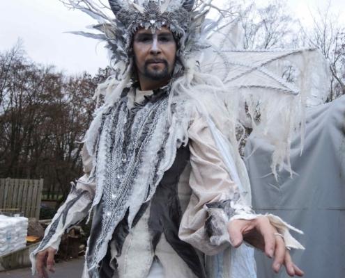 Weisse, gehörnte Gestalt im prunkvollen Kostüm