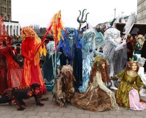 Künstlerensemble in phantastischen farbenfrohen Kostümen und Masken vor den Hamburger Alsterarkaden