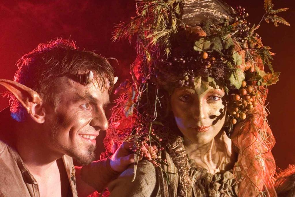 Stimmungsvolles Bild von Schauspieler mit Hörnern mit langen Ohren und Schauspielerin mit floralem Kopfschmuck in warmen Farben