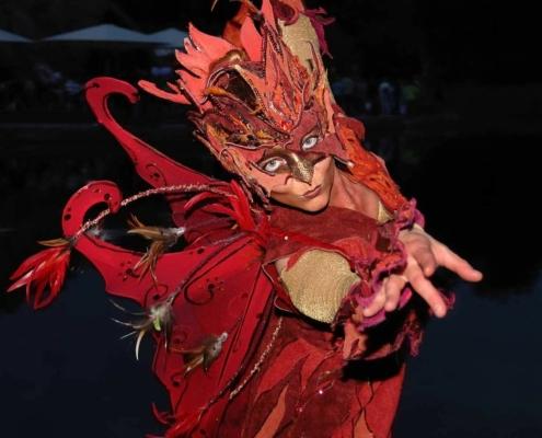 Tänzerin in feurig rotem Lederkostüm mit vogelartiger Maske