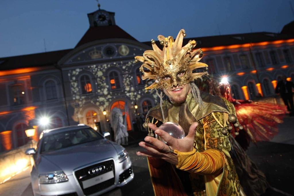 Artist mit goldener Narrenkappe jongliert mit Kristallkugel vor festlich iluminierten Anwesen