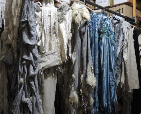 Weisse und blaue Kostüme hängen auf Kleiderbügeln an einer Garderobenstange