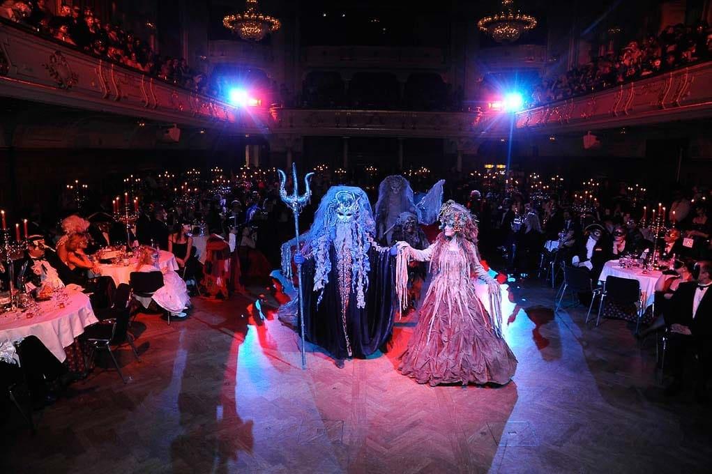 In einem festlich beleuchteten Ballsaal treten phantastisch gekleidete Künstler auf die Tanzfläche