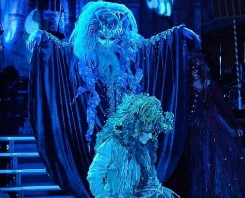 Bühnenszene mit phantastisch kostümierten Wesen in blauem Licht