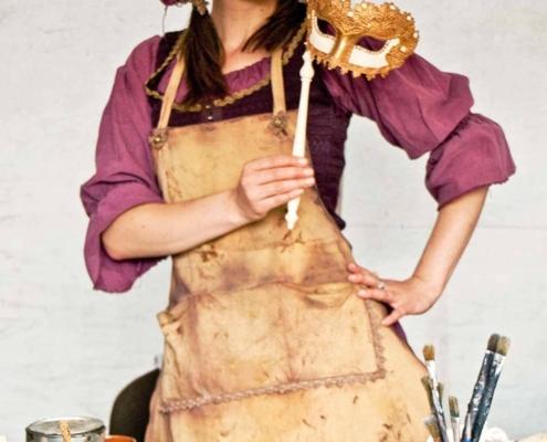 Maskenbau-Künstlerin im historischen Handwerker-Gewand und Stabmaske in der Hand