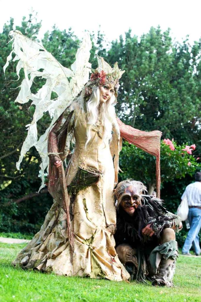 Feenkönigin mit goldenem Kleid, Krone und grossen Flügeln und ein gnomartiges Wesen das zu ihren Füssen kauert.