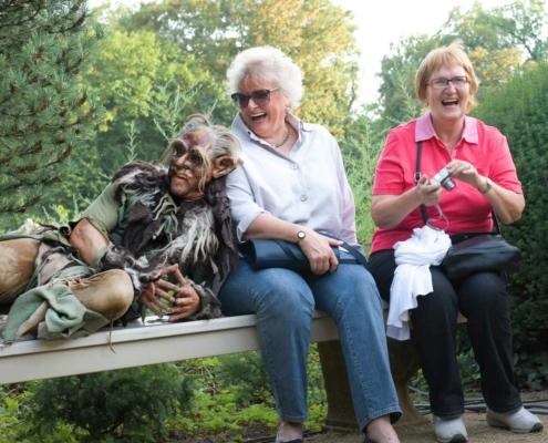 Koboldartiges Wesen liegt auf einer Bank und lehnt an einer lachenden älteren Dame