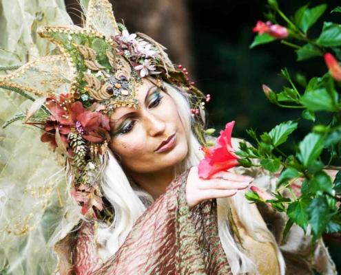 Schöne Frau mit Kostüm und schöner Krone posiert verträumt mit einer Hibiskusblüte