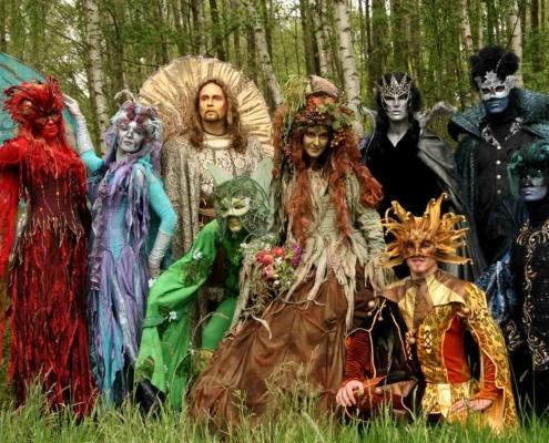 Gruppe von Künstlern in phantastischen, farbenfrohen Kostümen in natürlicher Wiesen- und Wald-Landschaft