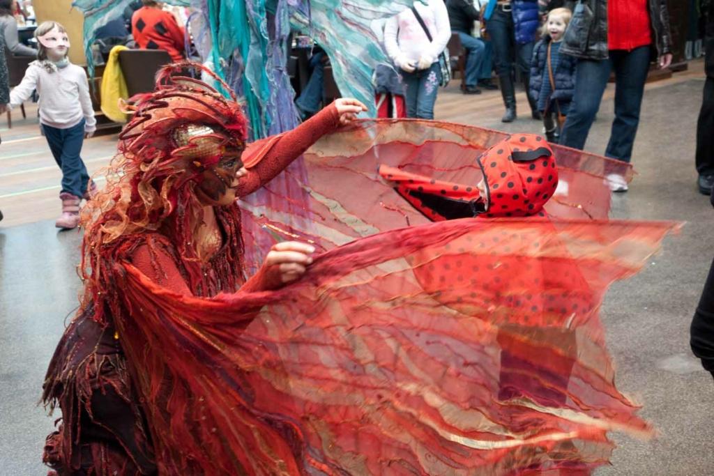 Frau in phantastischem roten Karnevalskostüm umfängt mit durchscheinenden Flügeln ein Kind in Käferkostüm